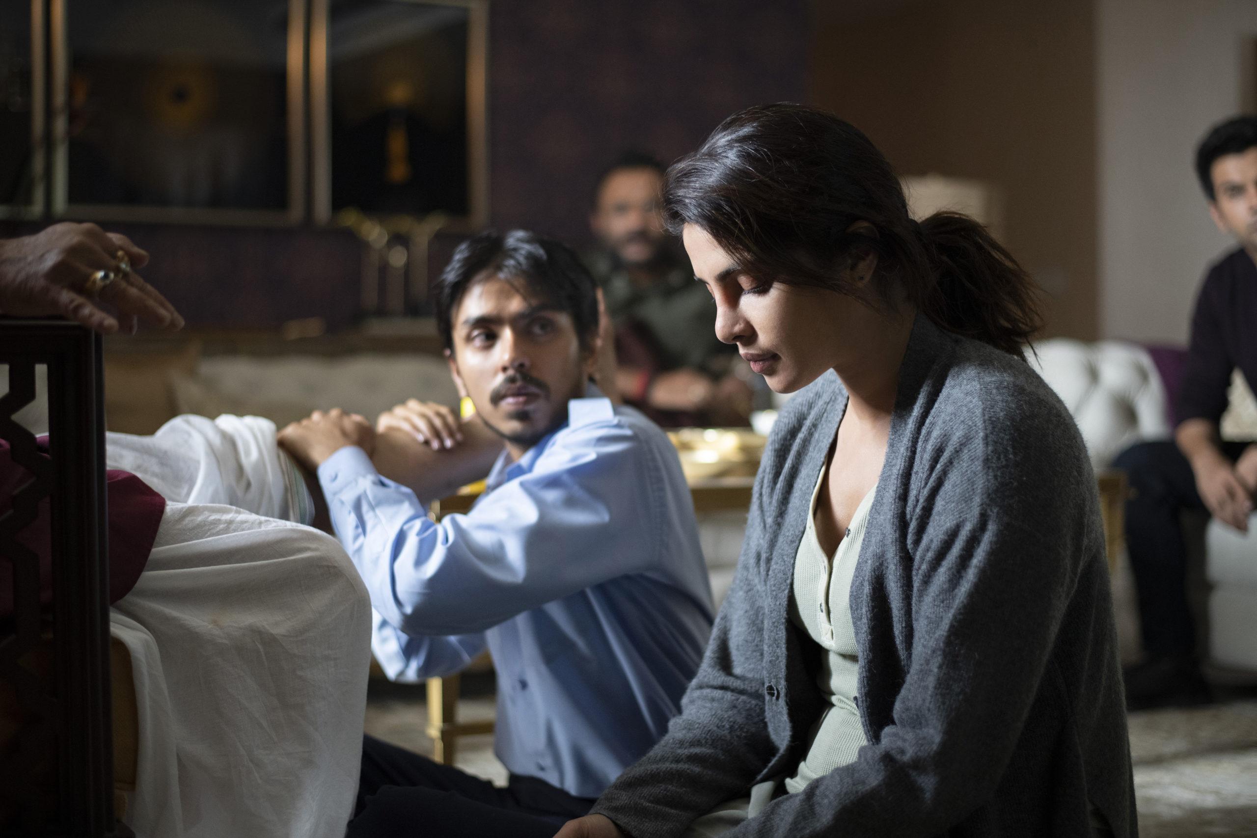 El personaje de Balram masajea la pierna de su amo junto a la señorita Pinky.
