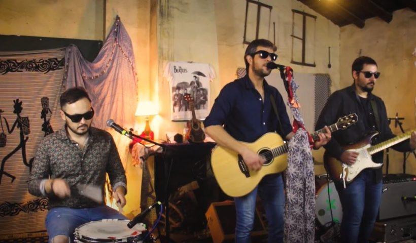 Tres componentes de la banda Ramone de Don Benito tocando. Uno tocando la caja sentado, otro cantando y tocando la guitarra y el tercero tocando la guitarra.