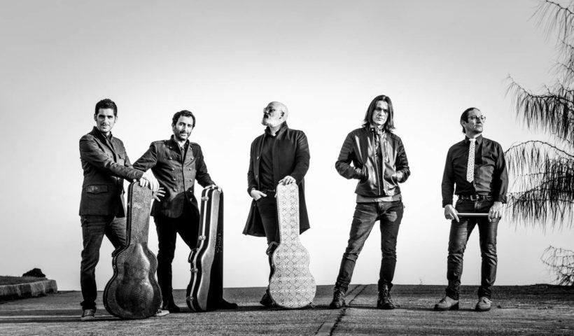 Fotografía en blanco y negro de los miembros de la banda Heiser que aparecen de pie en una carretera junto con algunos de sus instrumentos